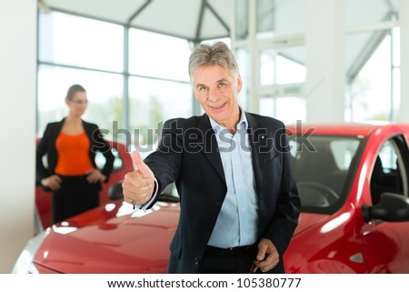 Mature single man with red auto in light car dealership with a female customer, a young woman, he is obviously buying a car or is a car dealer - stock photo