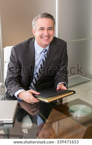 Mature smiling business man with a notebook in an office - stock photo