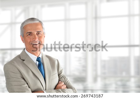 Mature smiling business manager crossing his arms in front of a large office window. Horizontal format with copy space. - stock photo