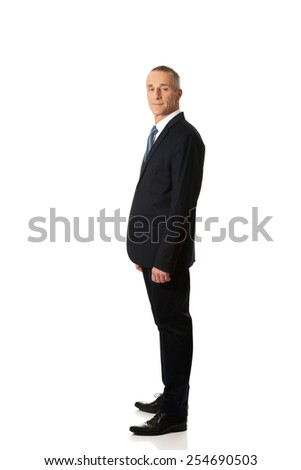 Mature smiling confident businessman standing. - stock photo