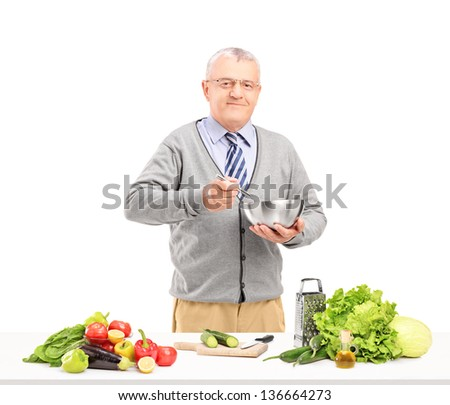 Mature smiling gentleman preparing a fresh salad isolated on white background - stock photo
