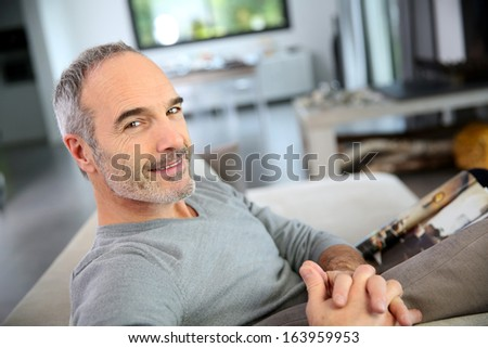 Mature smiling man sitting in couch at home - stock photo