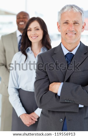 Mature smiling manager in a formal suit followed by two young business people - stock photo