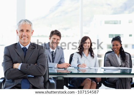 Mature smiling manager sitting with his arms crossed and with his team behind him - stock photo