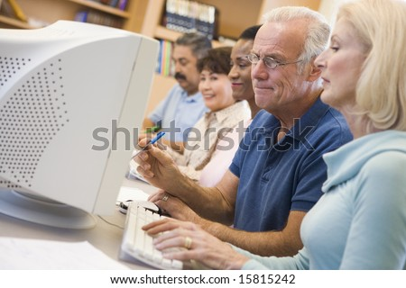 Mature students learning computer skills - stock photo