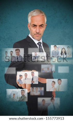 Mature stylish businessman using futuristic interface showing partners - stock photo