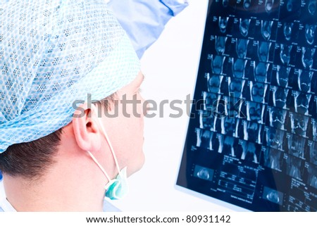 Mature surgeon man with protective mask review magnetic resonance imaging isolated on white background - stock photo