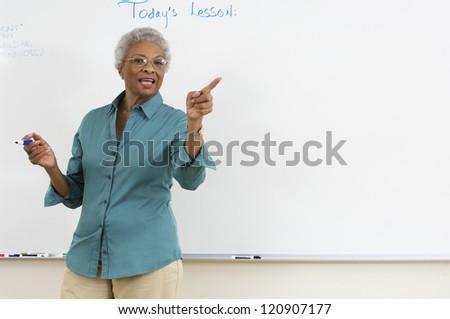 Mature teacher explaining lesson in classroom - stock photo
