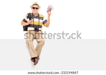 Mature tourist holding passport with money seated on a panel isolated on white background - stock photo