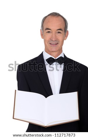 mature waiter holding out menu - stock photo