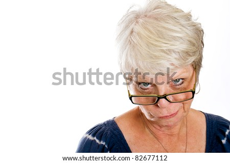 Mature, white haired woman with a skeptical expression on her face while looking over the rim of her glasses. - stock photo