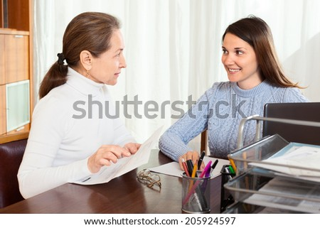 Mature woman and girl working with documents at office - stock photo