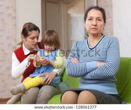 Mature woman and young mother with baby after quarrel at home - stock photo