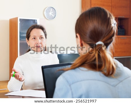 Mature woman answer questions of social worker in home - stock photo