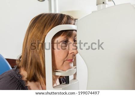 Mature Woman At Ophthalmologist Doing Examination Of The Eyes Looking Through Autorefraktometer - stock photo