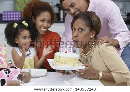 Mature woman blowing out the candles on her birthday cake - stock photo