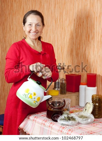Mature woman brews herbs in a teapot at home kitchen - stock photo
