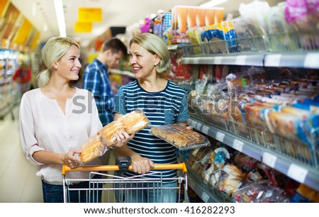 Mature woman choosing pastry in bakery section of a supermarket  - stock photo