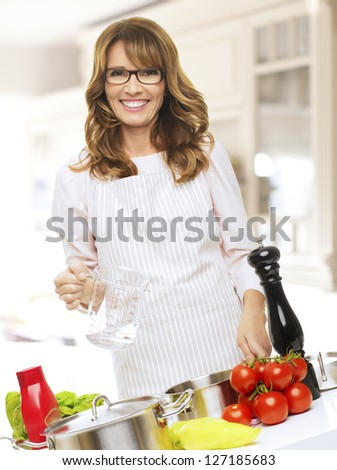 Mature Woman Cooking In The Kitchen - stock photo