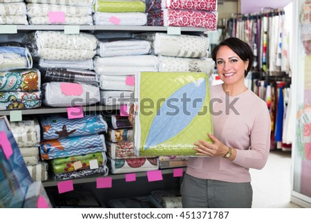 Mature woman customer handles bedspread near textiles shelves inside - stock photo