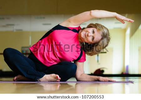 Mature Woman Does Yoga Side Bend - stock photo