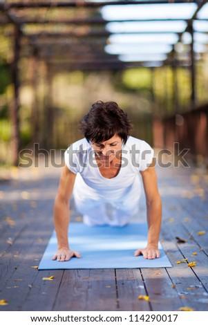 mature woman doing push ups outdoors - stock photo