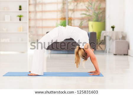 mature woman doing yoga at home - stock photo