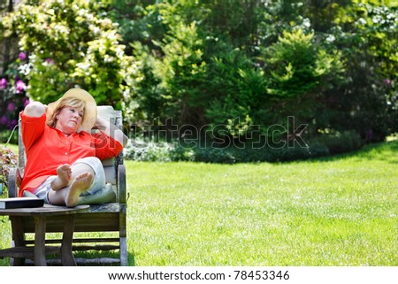 Mature woman dozing off in a sunny garden chair - stock photo