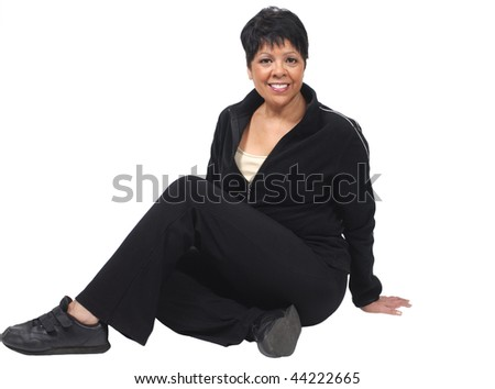 mature woman dressed in jogging outfit sitting isolated on white - stock photo