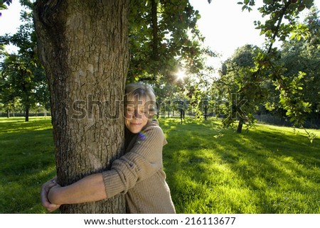 Mature woman embracing tree, eyes closed (lens flare) - stock photo