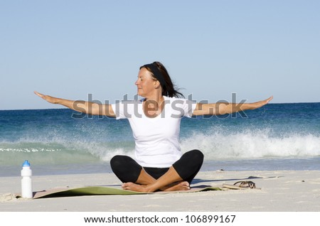 Mature woman exercising at beach, keeping healthy and fit with yoga and pilates, isolated with ocean and blue sky as background and copy space. - stock photo