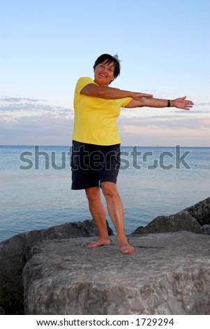 Mature woman exercising outside - stock photo