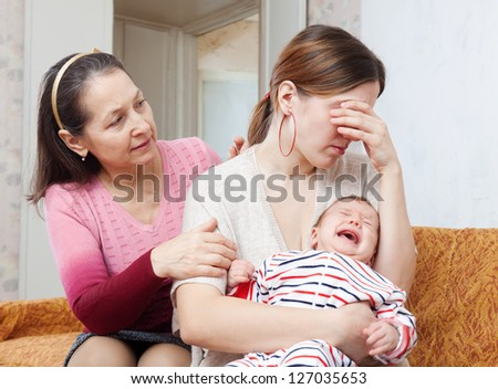 Mature woman gives solace to crying adult daughter with baby at home - stock photo