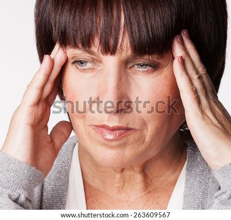 Mature woman has a headache. Sad female - stock photo