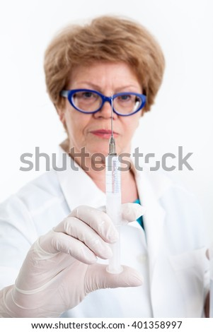 Mature woman healthcare worker looking at syringe for vaccination in her hand, focus on needle, white background - stock photo