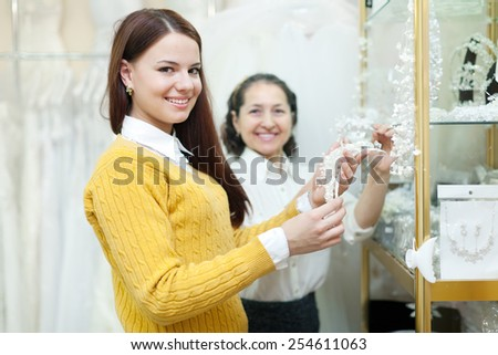 Mature woman helps the bride in choosing bridal accessories at shop of wedding fashion. Focus on girl - stock photo