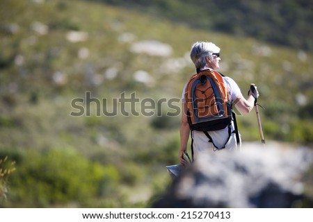 Mature woman hiking on mountain trail, carrying rucksack and using hiking pole, rear view - stock photo