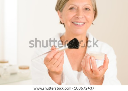 Mature woman hold brush and make-up powder in the bathroom - stock photo