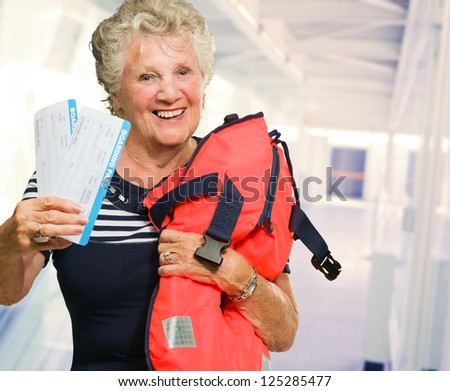 Mature Woman Holding Boarding Pass And Bag, Indoors - stock photo