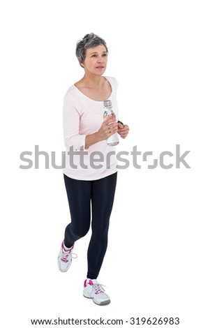 Mature woman holding bottle while jogging against white background - stock photo