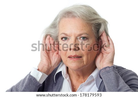 Mature woman holding hands to ear - stock photo