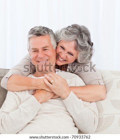 Mature woman hugging her husband at home - stock photo