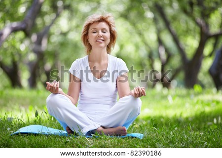 Mature woman in a park yoga - stock photo
