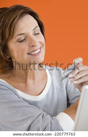 mature woman in casual clothing shopping over the internet - stock photo