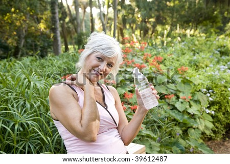 Mature woman in her 50s in workout clothes drinking a bottle of water, leaning on wooden railing in park - stock photo