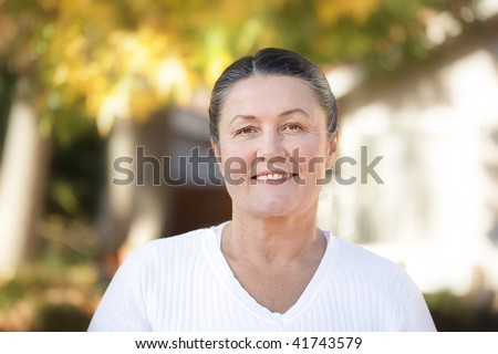 Mature woman in her sixties standing outside on a bright autumn day - stock photo