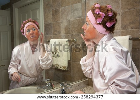 Mature woman in pink bathrobe wearing curlers and applying facial mask standing at the bathroom sink - stock photo