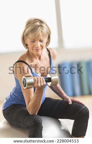 Mature woman lifting dumbbell while sitting on fitness ball at home - stock photo