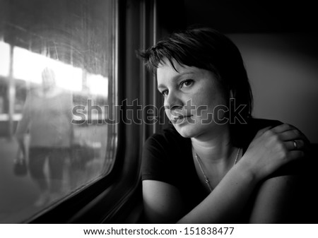 Mature woman looking into the window of the train. Real people series. - stock photo