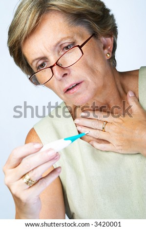 Mature woman looking scared when reading temperature on the thermometer - stock photo